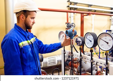Technician worker on oil and gas refinery checks pressure manometers