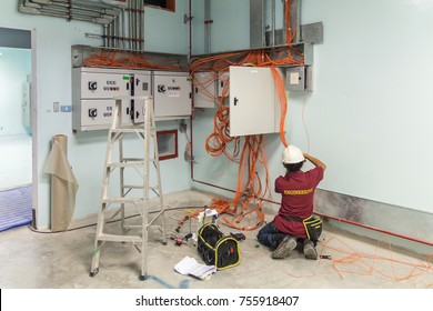 Technician or worker wear helmet and wiring cable of electrical control panel in building room