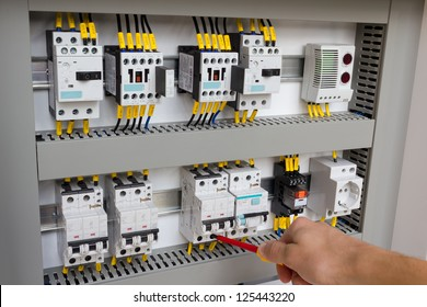 Technician working at electrical cabinet (using a screwdriver).