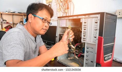 Technician working on broken computer in his office.