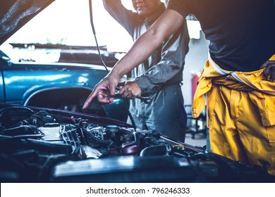 technician working on checking and service car in  workshop garage; technician repair and maintenance engine of automobile in car service
