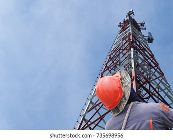 Technician working on Communication tower with sunset blue sky background