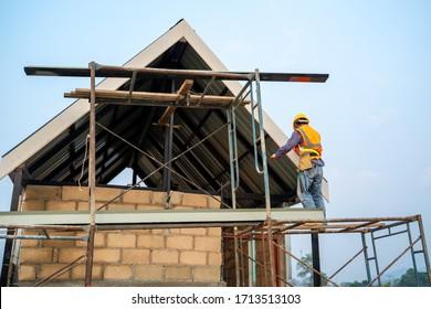 Techniker, der an der Dachstruktur auf der Baustelle arbeitet,Bauarbeiter, der beim Arbeiten an der Dachstruktur des Gebäudes auf der Baustelle Sicherheitsgurte trägt.