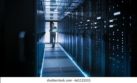IT Technician Works on Laptop in Big Data Center full of Rack Servers. He Runs Diagnostics and Maintenance, Sets System Up.