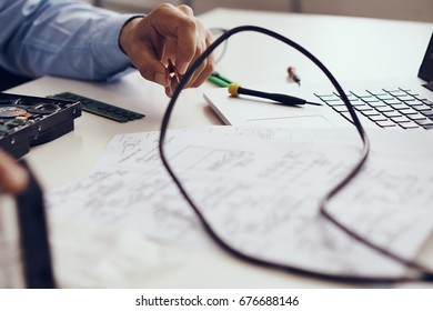 Technician-programmer with computer parts, wires, repair