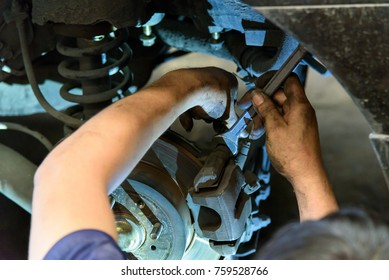 Technicians are changing car shock absorbers.
