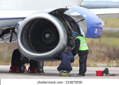 Technicians checking jet engine of civil airplane.