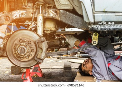Technicians in grey uniform are repairing the axle of a car, which is the car's propulsion system, Automotive industry and garage concepts.