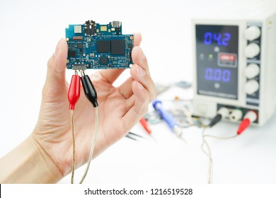 Technician's hand holding circuit board of cellphone and measuring the voltage with DC Power Supply on white background.Analysis to repair.Selective focus.