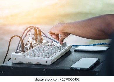 Technician's hand tuning adjustment on audio control panel in booth at the audio system equipment and control panel of digital studio mixer. Hand tuning Sound control knob on amplifier.