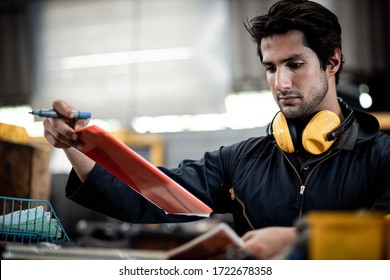 Technicians man or engineer holding a document for checking work in a heavy industrial factory behind. The Maintenance looking of working at industrial machinery and check security system setup.