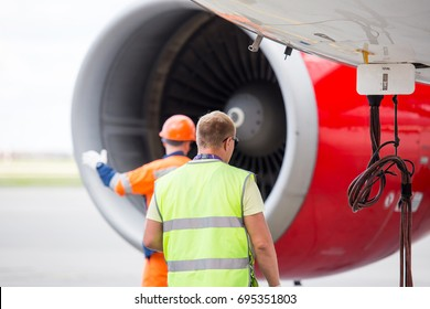 Technicians in signal vests prepare the aircraft for flight. Inspection and maintenance of the aircraft engine.