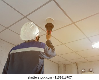 Technicians are testing smoke alarm on white ceiling.
