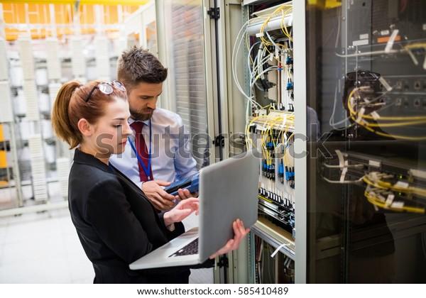Techniker, die Laptop verwenden, während sie Server im Serverraum analysieren