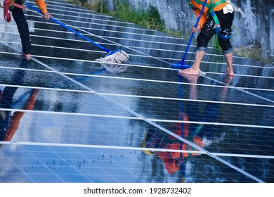 Technicians are using a mop and water to clean the solar panels that are dirty with dust and birds' droppings to improve the efficiency of solar energy storage even better. Soft and selective focus.