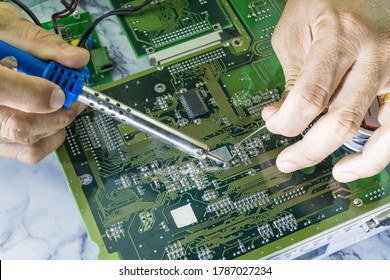 Technicians are using a soldering iron for repairing electronic of the computer circuit board concept technology of computer circuit hardware.