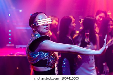 Techno dancer in night club dancing to the beat of music from DJ . EDM new year night party and nightlife concept .