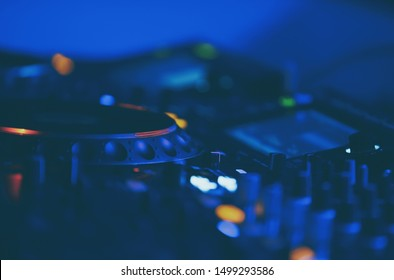 Techno music party in night club.Dj turntables and sound mixer for playing musical tracks at edm festival.Professional disc jockey audio setup in blue stage lights.Play and remix songs with turn table