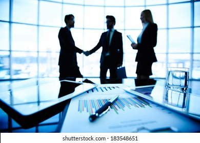 Technological devices, financial document with pen, glass of water at workplace on background of three business partners striking deal