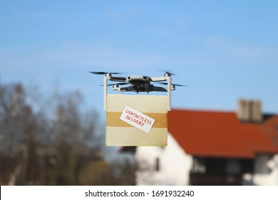 Technological shipment innovation - drone fast delivery concept, multicopter flying with cardboard box to deliver package to a private house in the background (purposely blurred)