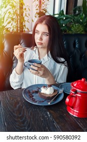 technologies, emotions, lifestyle, people, teens concept -Young happy female reading on her mobile phone while sitting in modern coffee shop interior, girl with beautiful smile. drink tea