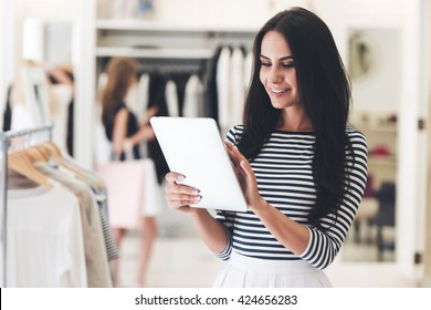Technologies make business easier. Beautiful young woman using her digital tablet with smile while standing at the clothing store