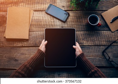 Technologies make life easier. Close-up top view image of woman holding digital tablet with copy space while sitting at the rough wooden table
