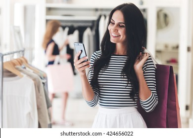 Technologies make shopping easier. Beautiful young woman with shopping bags using her smart phone with smile while standing at the clothing store