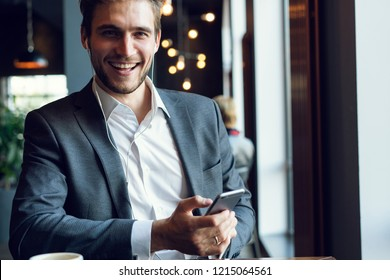 Technologies making life easier. Young business man drinking coffee in cafe and using phone