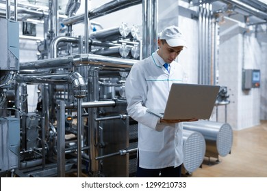 Technologist with a laptop in his hands at the dairy plant