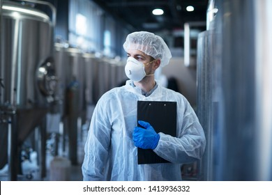 Technologist in protective white suit with hairnet and mask standing in food factory.