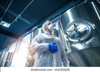 Technologist in protective white suit with hairnet and protection mask working in production plant. Low angle view of industrial worker in food factory.