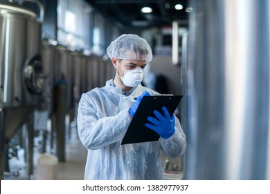 Technologist specialist keeping track of production process and writing notes in his logbook. Responsible young man at his workplace.