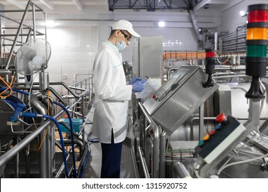 Technologist stands with a tablet near the digital screen at the dairy Plant