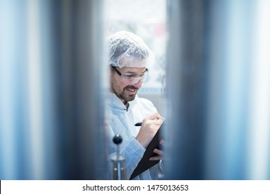 Technologist in white protective suit standing by industrial machines and writing report on quality control. Food processing industry.
