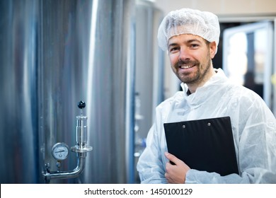 Technologist in white protective uniform and hairnet standing by chrome reservoirs with pressure gauge in food processing plant. Smiling technologist expert holding checklist. Industrial worker.