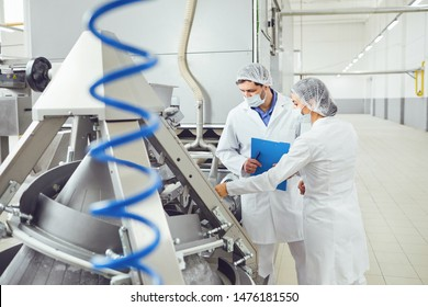 Technologists inspector in masks at food factory.