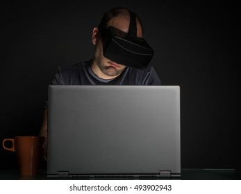 Technology addicted man at home at night on gray background. Virtual reality addiction concept.