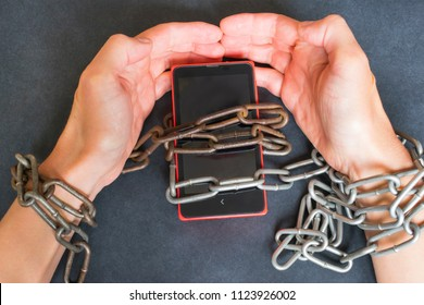 Technology addiction concept, smartphone and chains on the dark background.