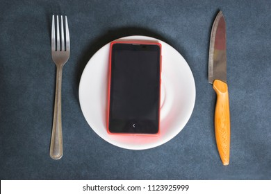 Technology addiction concept, smartphone on a plate on the dark background.