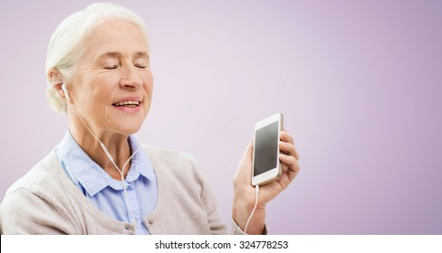 technology, age and people concept - happy senior woman with smartphone and earphones listening to music over violet background