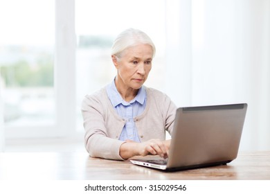 technology, age and people concept - senior woman with laptop computer at home