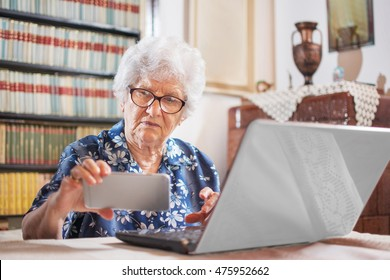 Technology, age and people concept. Senior woman using smartphone and laptop at home.