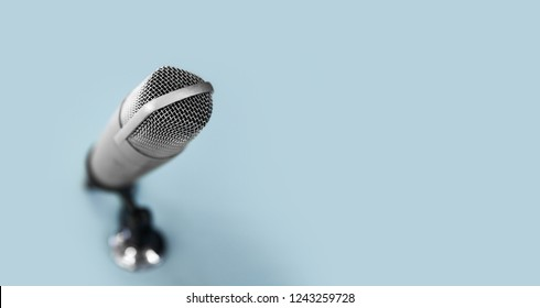 technology and audio equipment concept - close up of microphone at recording studio or radio station on blue background