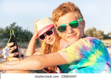 Technology and beach concept. Teenagers (boy and girl) using smart phone and listening music with headphone on the beach. Happy teens are wearing colorful sunglasses and having fun. Summer holidays.