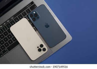 Technology blue work space a macbook pro and two iPhone 12 pro: Rome, Italy, february 01, 2021