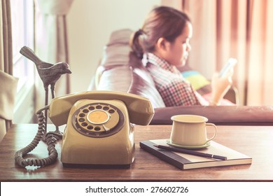 Technology change concept, young woman use smartphone near old telephone on wooden table
