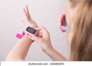 Technology for children: a girl wearing pink glasses uses a smartwatch. Portrait.
