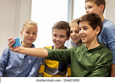 technology, children and people concept - group of happy kids or friends taking selfie with smartphone