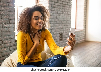 Technology. Communication. Afro American girl in earphones is smiling while talking on the smartphone; sitting on a bean bag chair at home